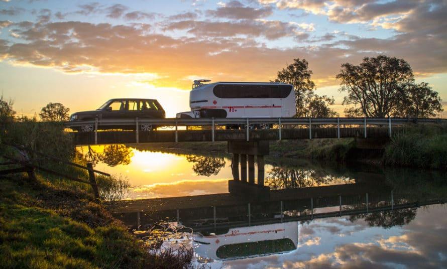 caravan over bridge at sunset